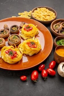 濃い灰色のテーブル皿に調味料を入れた正面のおいしいきのこ料理生の熟した食品