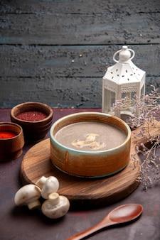 Vista frontale gustosa zuppa di funghi con diversi condimenti sullo spazio buio
