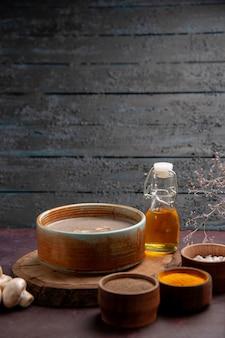 濃い紫色の空間にさまざまな調味料を使ったおいしいキノコのスープを正面から見る