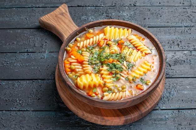 紺色のデスクカラー料理料理イタリアンパスタスープに緑のスパイラルイタリアンパスタからの正面のおいしいパスタスープ