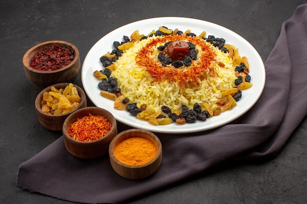 Front view tasty plov famous eastern meal consists of cooked rice and raisins on dark space