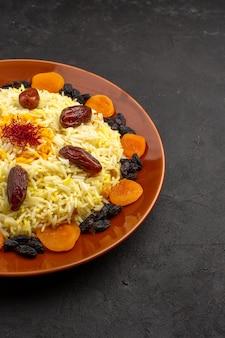 Вкусный плов, вид спереди, знаменитая восточная еда, состоящая из вареного риса и изюма на темном пространстве.