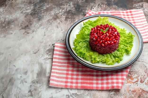 Vista frontale gustosa insalata di melograno a forma rotonda su insalata verde su dieta di pasto maturo di salute di colore chiaro