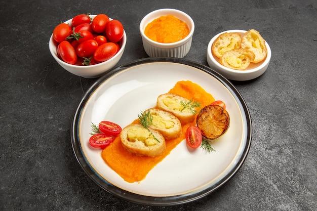 正面図灰色の背景にカボチャとフレッシュトマトのおいしいポテトパイを焼くディナーオーブンの色の皿熟した