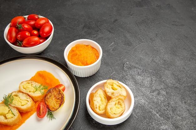 正面図灰色の背景にカボチャとフレッシュトマトのおいしいポテトパイディナーオーブン焼き色皿スライス
