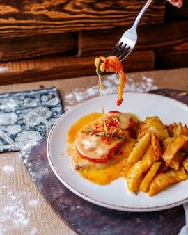茶色の表面の白いプレート内の調理された野菜と一緒に正面のおいしいジャガイモ