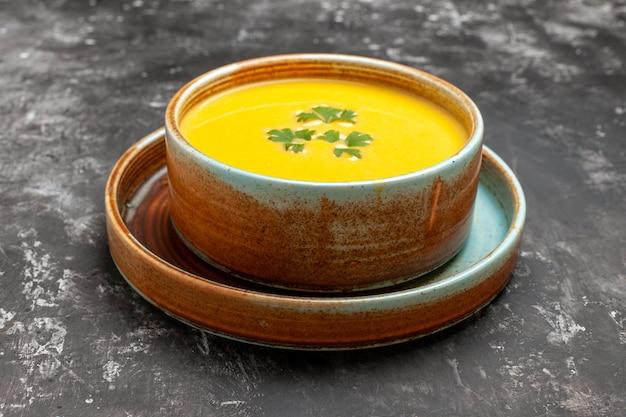 Вид спереди вкусный тыквенный суп внутри тарелки на темном столе, блюдо для фруктового супа