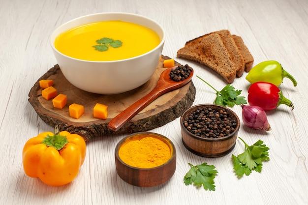 Vista frontale gustosa zuppa di zucca con pagnotte di pane scuro e condimenti su spazio bianco