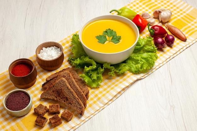Вид спереди вкусный тыквенный суп с разными приправами и хлебом на белом пространстве