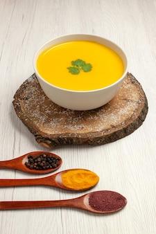 白い空間に調味料を入れた正面おいしいかぼちゃスープ