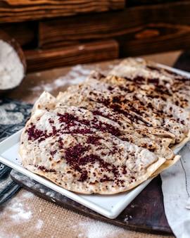 Вид спереди вкусная мясная мука qutabs с sumax внутри белой тарелке на коричневой поверхности