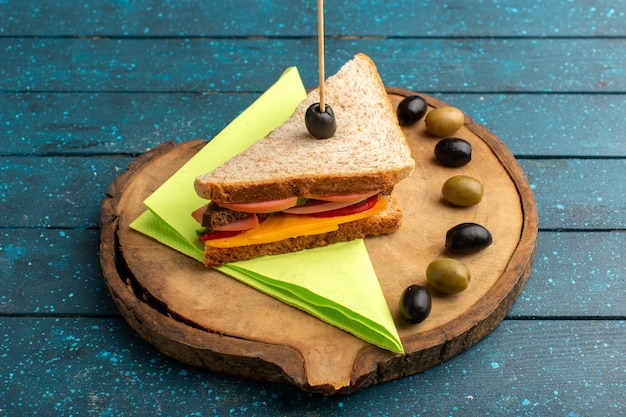 Front view tasty sandwich with cheese ham inside with olives on blue wooden desk