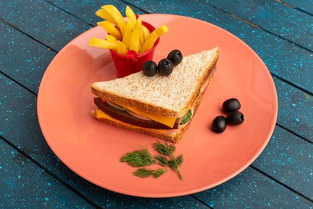 青い木のフライドポテトとピンクプレート内のオリーブハムトマトと正面のおいしいサンドイッチ