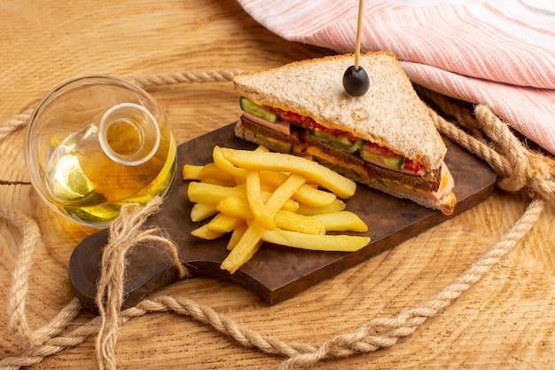 Вид спереди вкусный бутерброд с оливками, ветчиной, помидорами, овощами и картофелем фри, веревками, маслом на дереве