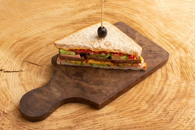 Вид спереди вкусный бутерброд с оливковой ветчиной, помидорами, овощами на дереве