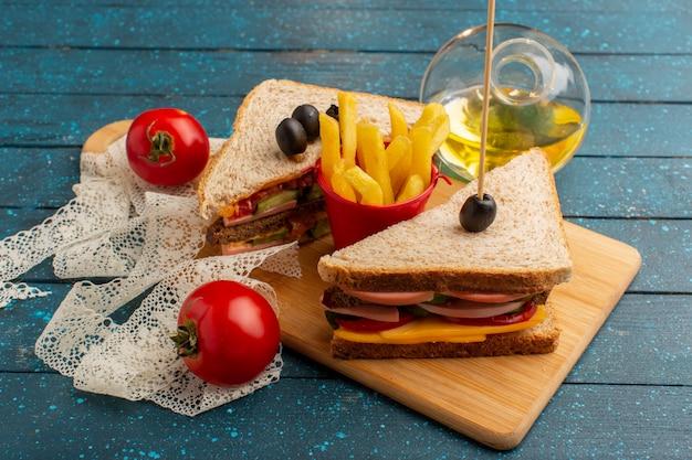 Vista frontale gustosi panini con prosciutto d'oliva pomodori patatine fritte olio e toamtoes su legno