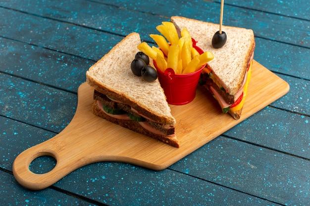 Вид спереди вкусные бутерброды с оливковой ветчиной, помидорами, картофелем фри на дереве