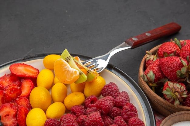 Вид спереди вкусные нарезанные фрукты со свежими ягодами и фруктами на темных мягких экзотических тропических фруктах здорового образа жизни
