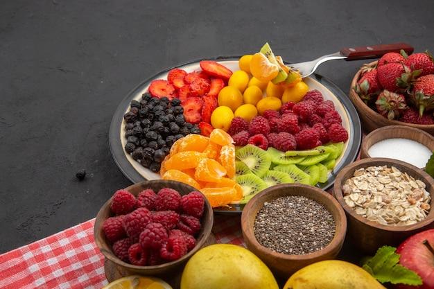 어두운 부드러운 열대 과일의 건강한 삶에 신선한 딸기와 과일을 곁들인 맛있는 얇게 썬 과일