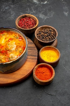 Vista frontale gustosa zuppa con condimenti su uno spazio grigio scuro