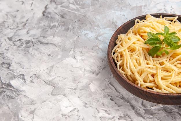 白いテーブルの食事皿生地パスタに緑の葉と正面図おいしいスパゲッティ