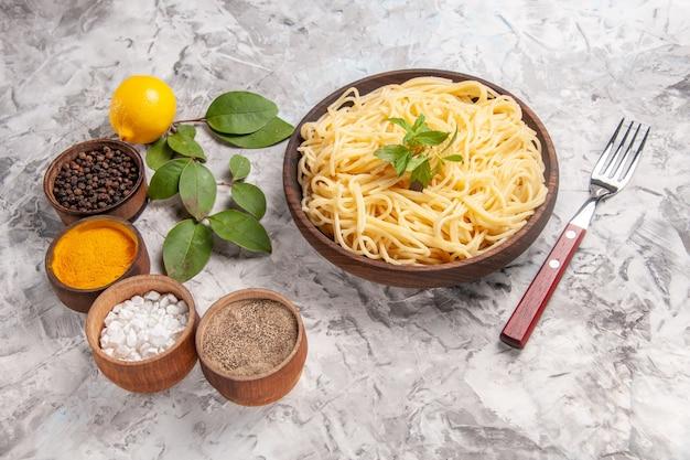 Spaghetti saporiti di vista frontale con i condimenti sul piatto di pasta del pasto dell'impasto della scrivania bianca