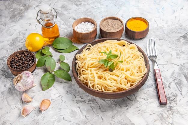 Vista frontale gustosi spaghetti con condimenti su pasta bianca da tavola piatto di pasta pasto