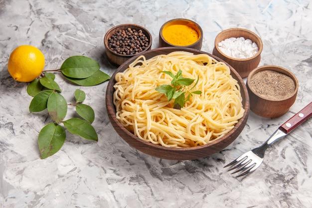 Spaghetti saporiti di vista frontale con i condimenti sul piatto di pasta del pasto della pasta della tavola bianca