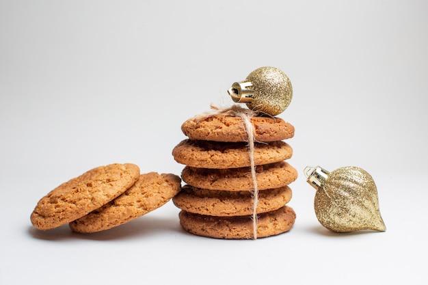 Vista frontale gustosi biscotti dolci su biscotto bianco dessert tè foto torta zucchero
