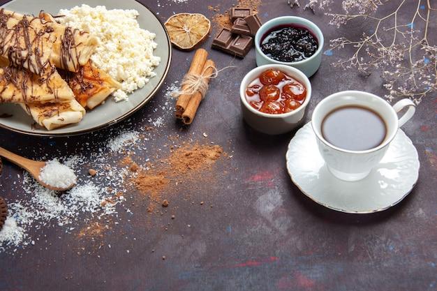Pasticcini dolci gustosi vista frontale con tazza di tè e marmellata su uno spazio buio