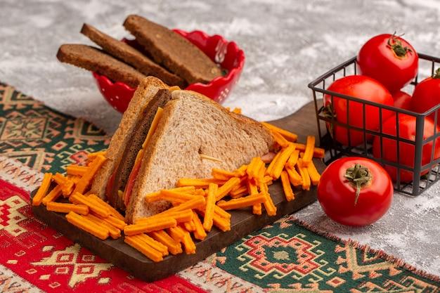 Вид спереди вкусный бутерброд с тостами с сырной ветчиной вместе с картофелем фри, хлебцами, помидорами на белом