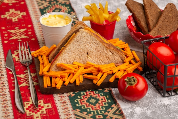 Front view tasty toast sandwich with cheese ham along with french fries sour cream tomatoes on white