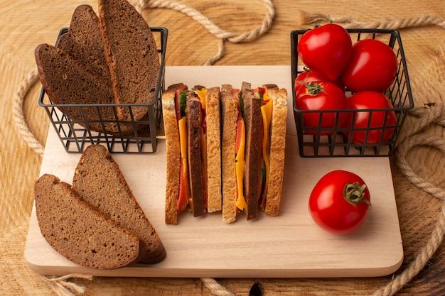 木製の机の上の赤いトマトのパンと一緒にチーズハムと正面のおいしいトーストサンドイッチ