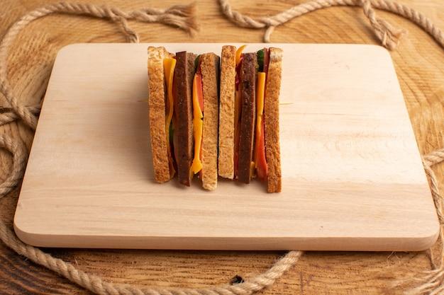 Вид спереди вкусный бутерброд с тостами с сырной ветчиной на дереве