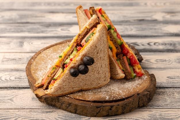 Вид спереди вкусные бутерброды с тостами с сырной ветчиной внутри на дереве