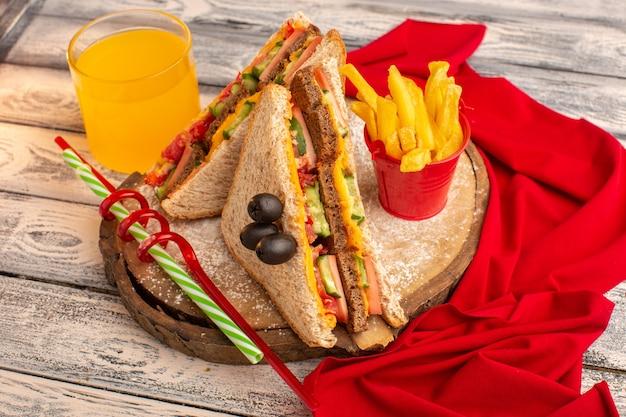 Вид спереди вкусные бутерброды с тостами с сырной ветчиной внутри с соком картофель фри красная ткань на дереве