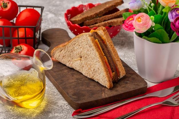 Вид спереди вкусные бутерброды с тостами с сырной ветчиной, масляными помидорами и цветами на белом