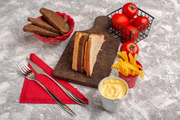 Vista frontale gustosi toast panini con formaggio, prosciutto, olio, pomodori, patatine fritte e panna acida su bianco