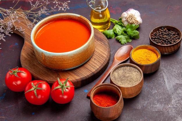Vista frontale gustosa zuppa di pomodoro con pomodori freschi e condimenti su spazio buio