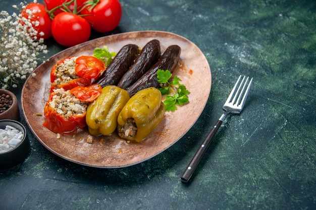 Vista frontale gustoso dolma vegetale pasto riempito con carne macinata su sfondo blu