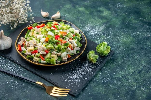 Vista frontale gustosa insalata di verdure all'interno del piatto su sfondo blu scuro