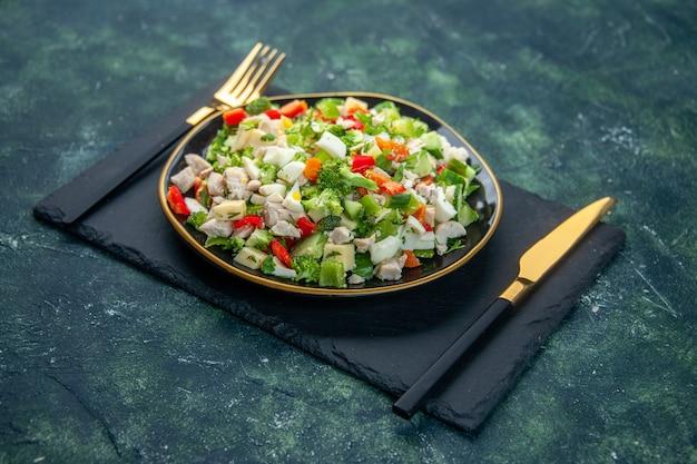 Vista frontale gustosa insalata di verdure all'interno della piastra con forchetta su sfondo scuro