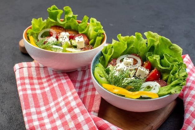 暗い背景にチーズきゅうりとトマトの正面図おいしい野菜サラダ