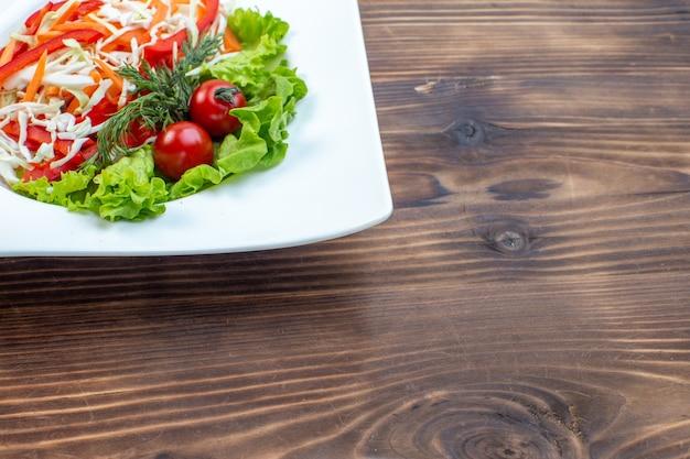 茶色の表面のプレートの内側にグリーンサラダとキャベツを添えた正面図のおいしい野菜サラダ