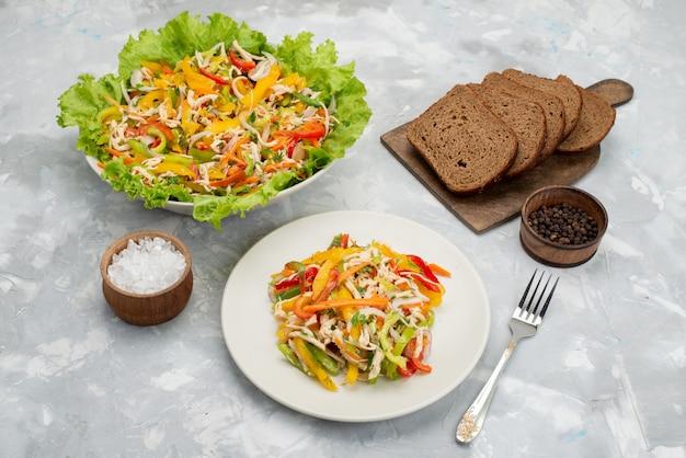 Вид спереди вкусный овощной салат с нарезанными овощами и зеленым салатом с буханками хлеба на сером, овощной салат, еда, еда
