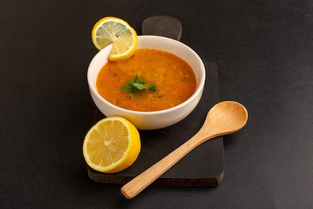 暗い背景にレモンと一緒にプレート内のおいしい野菜スープの正面図。