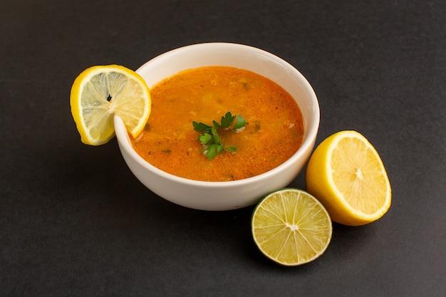 暗い机の上のレモンと一緒にプレートの内側の正面図のおいしい野菜スープ。