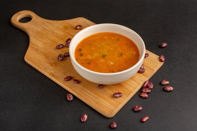 暗い机の上の生豆と一緒にプレート内の正面図のおいしい野菜スープ。
