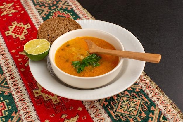 暗い机の上にパンとレモンが入ったプレートの内側の正面図のおいしい野菜スープ。