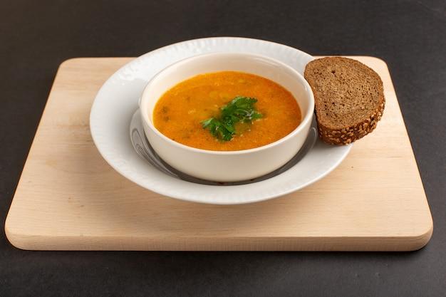 暗い机の上にパンの塊が付いているプレートの内側の正面図のおいしい野菜スープ。